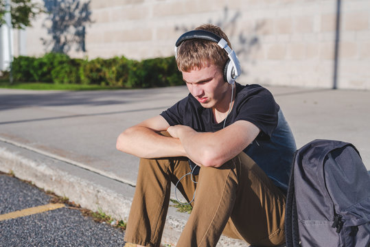 Sad teenage boy sitting on curb near school while listening to music on his headphones.
