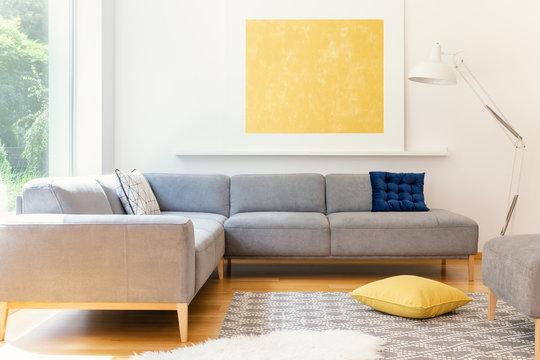A minimalist, yellow poster and a white, industrial floor lamp in a sunny living room interior with a patterned rug and vibrant decorations