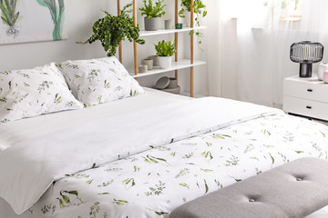 Close-up of a bed dressed in organic cotton green plants pattern white linen in a sunny bedroom interior. Real photo.