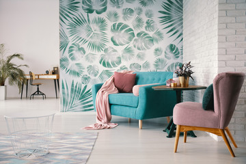 Chair and turquoise sofa in green living room interior with leaves wallpaper and table. Real photo Wall mural