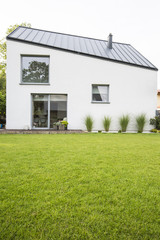 Green lawn in the backyard of a luxurious house with wooden terrace in the summer. Real photo