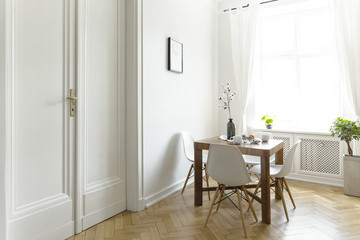 A small wooden dining table with chairs in a sunny room interior with white walls, double door and a window. Real photo.