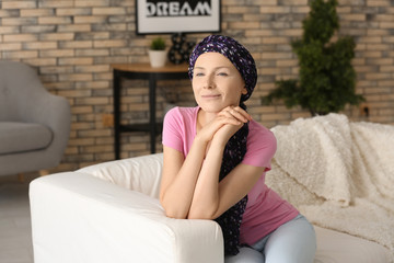 Happy woman after chemotherapy  sitting on sofa at home