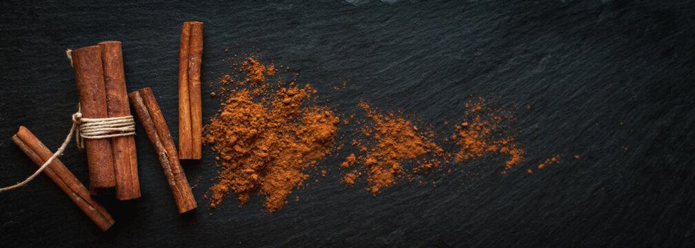 Ground cinnamon and cinnamon sticks on dark background, top view, text space