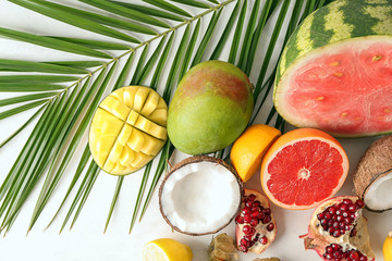 Various delicious fruits with tropical leaf on light table