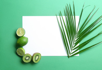 Composition with various delicious fruits, tropical leaf and blank card on color background