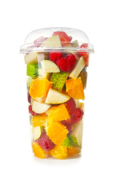 Delicious fruit salad in plastic cup on white background
