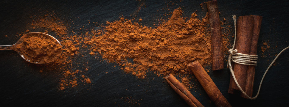 Ground cinnamon in teaspoon, and cinnamon sticks on dark background, top view, text space