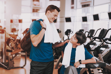 Young Father and Son near Treadmills in Modern Gym