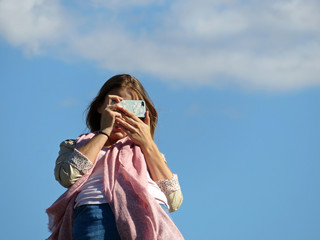 Girl taking pictures with a smartphone camera, the bottom view. Young woman photographer outdoors, isolated on blue sky background, inspiration concept