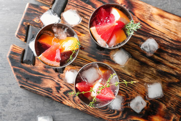 Glasses of refreshing grapefruit lemonade on wooden board, top view