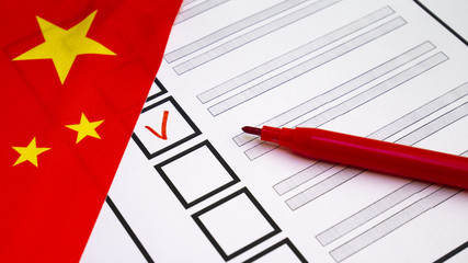 Voting in paper ballot by red pencil in China wirh Chinese flag