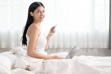 Woman shopping in bed.