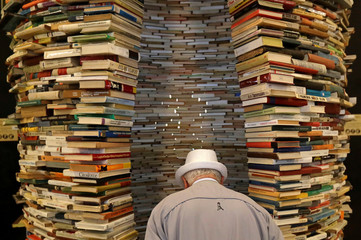 A man looks at books piled up at the entrance of Municipal Library of Prague in Prague