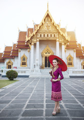 Woman tourist with red traditional Thai umbrella at Wat Benchamabophit the marble temple in Bangkok, Thailand