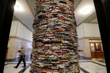A man walks past books piled up at the entrance of Municipal Library of Prague in Prague