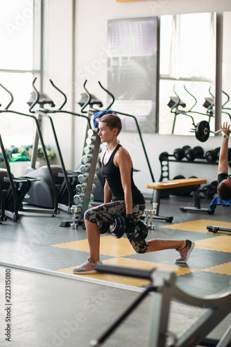 View of pretty healthy woman engaged in fitness in gym alone