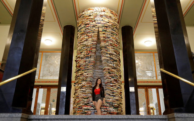 A woman poses in front of books piled up at the entrance of Municipal Library of Prague in Prague
