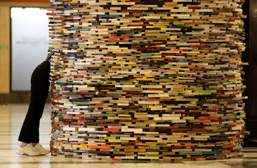 A woman looks at books piled up at the entrance of Municipal Library of Prague in Prague