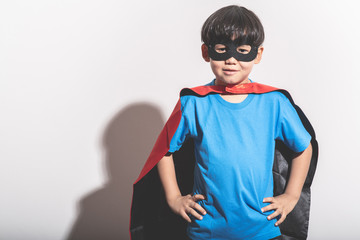 Young boy super hero portrait in white background with hard light.