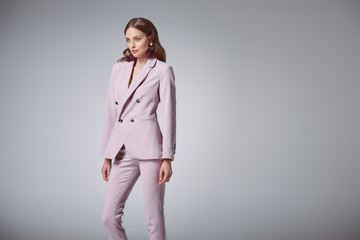 attractive woman in fashionable pink suit looking away isolated on grey
