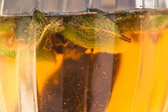 Carbonated soda water or juice with lime and mint in a glass jug. Macro closeup