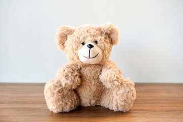 Cute Teddy Bear sitting alone with white cement wall on wooden table