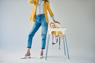 cropped shot of stylish mother standing near baby girl sitting in high chair on grey