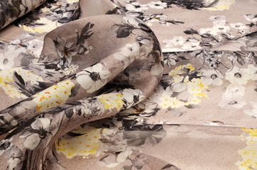 Organza silk fabric with a floral black-and-yellow-brown ornament