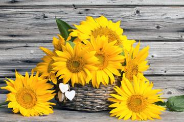 Sonnenblumen im Weidenkorb rustikal vor Holzhintergrund im Herbst