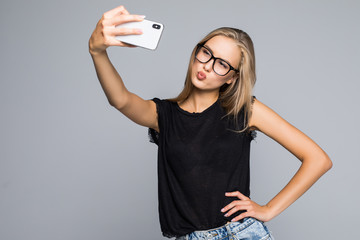 Happy cute woman making selfie on phone over gray background.