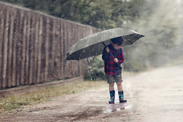 boy standing under umbrella in rain