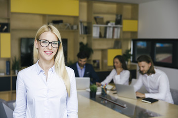 Young businesswoman standing in the office and other young business people working in the background