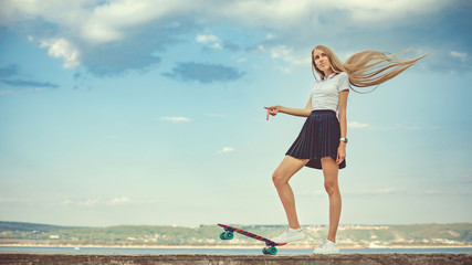 Cute girl is standing with her skateboard in hands. Street life. Urban style of life. Youth culture. Urban sport. Instagram style image. A lot of space for text.
