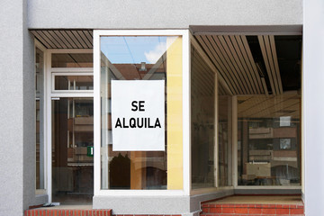spanish vacancy sign in empty shop window reads se alquila meaning for rent
