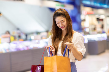 Beautiful Attractive Asian woman open shopping bags after shopping smile and enjoy with it in shopping mall so happiness and cheerful,Shopping Concept