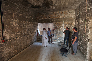 Iraqi men rebuild a house of a Christian man in the Christian city of Qaraqosh