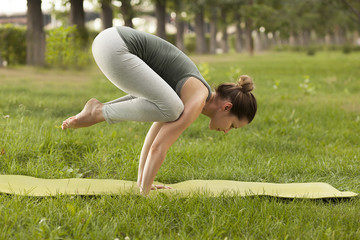Practice of yoga and gymnastics. Young girl doing yoga. Female yoga. Yoga in the Summer Park