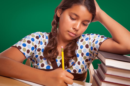 Hispanic Girl Student with Pencil and Books Studying with Chalk Board Behind