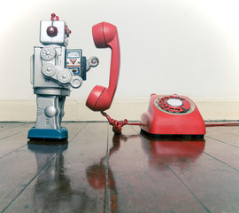 big silver robot toy on  a red phone standing