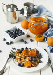 Homemade crepes served with apricot jam fresh blueberries.
