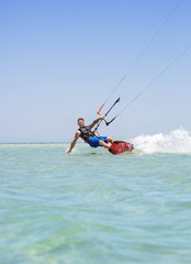 Man kiteboarding on turquoise water in el gonna, egypt