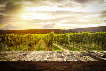 Foto auf Leinwand Weinberg old rustic table in a beautiful vineyard at sunset