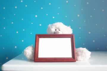 Empty photo wooden frame and white teddy bear in the nursery