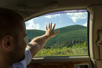 A view from the car's interior to the man who sits in the back seat and extends a hand in the window saying goodbye or greeting the nature and mountains of the Altai rejoicing in traveling by car