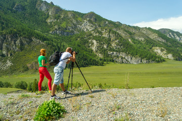 Young man photographer and red haired girl travels through the Altai with the camera on the tripod takes a shot of the snow-covered mountains and the rocks with turquoise winding river Katun