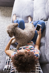 Lovely brown spanish water dog sitting on the sofa with her owner at home, Funny time together. Lifestyle photography. pets indoors