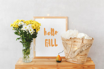 Frame with text HELLO FALL, vase with white and yellow chrysanthemums, wicker straw bag, pumpkin, glowing garland lights on a wooden table on background of light gray walls. Autumn home interior decor