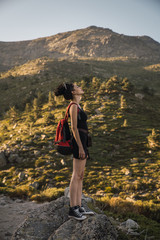 Young woman with backpack enjoying nature