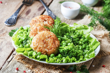 Fish cutlets or meatballs from cod and pike perch with a garnish of green peas and broccoli, rustic style, selective focus